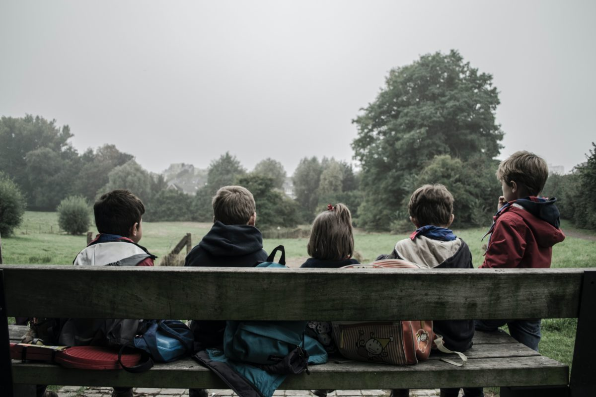 Children sitting on wooden bench with tree view in front of them