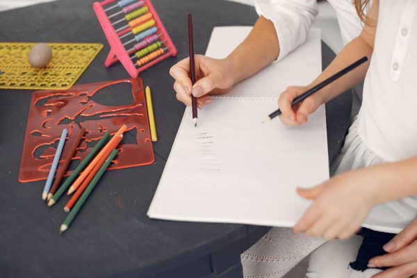 adult helping child draw with colored pencils
