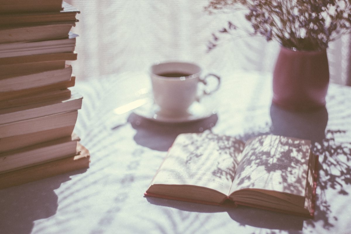 cup of tea next to large book pile