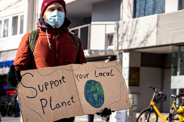 "Activists holding sign reading ""Support your Local Planet"""