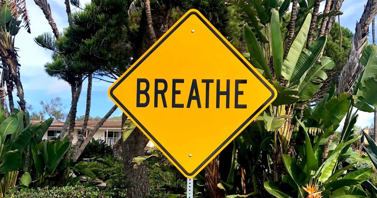 """a yellow street sign that says """"BREATHE"""""""