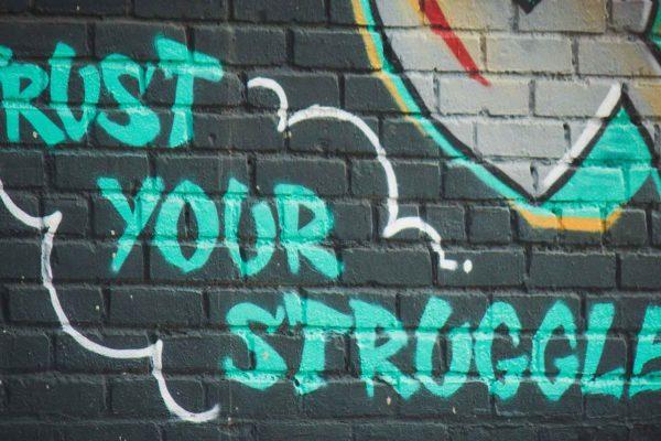 "bright graffiti on a dark blue brick building that reads ""Trust your struggle"""